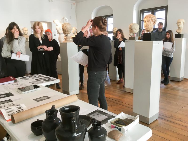 Mehrere Personen stehen verteilt in einem Ausstellungsraum zwischen mehreren Sockel mit Ausstellungsobjekten. Im Vordergrund ist ein Tisch mit Gefäßen und Abilldungen zu sehen.
