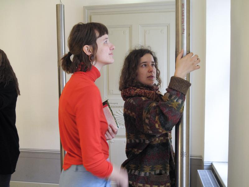 Zu sehen sind zwei Personen. Sie ertasten Brailleschrift an einem Ausstellungsobjekt des Bachmuseums.
