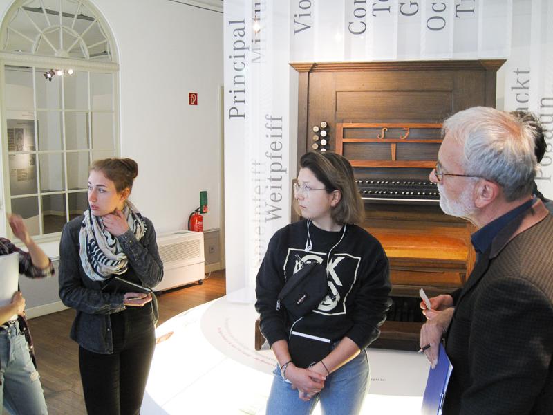 Im Vordergrund sind drei Personen zu sehen. Ihr Blick ist nach links gerichtet. Im Hintergrund befindet sich ein Ausstellungsobjekt der Dauerausstellung des Bachmuseums.