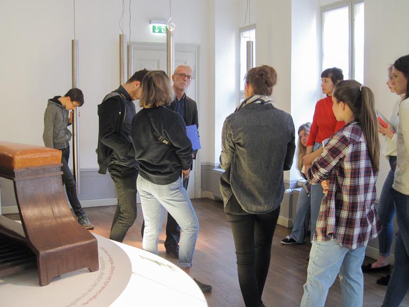 Zu sehen ist eine Gruppe von Personen. Sie stehen im Kreis in einem Ausstellungsraum.