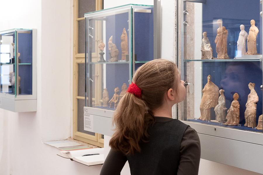 Zu sehen ist ein Mädchen in einem Ausstellungsraum. Sie betrachtet Ausstellungsobjekte in einer Vitrine an der Wand.