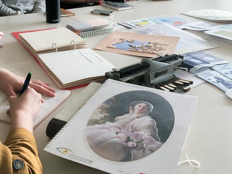 Zu sehen ist ein Tisch mit Reliefs und Druckerzeugnissen für Blinde und Menchen mit Seheinschränkungen. In der linken Bildhälfte ist eine Person zu sehen. Sie macht sich Notizen und es sind nur die Hände zu sehen.