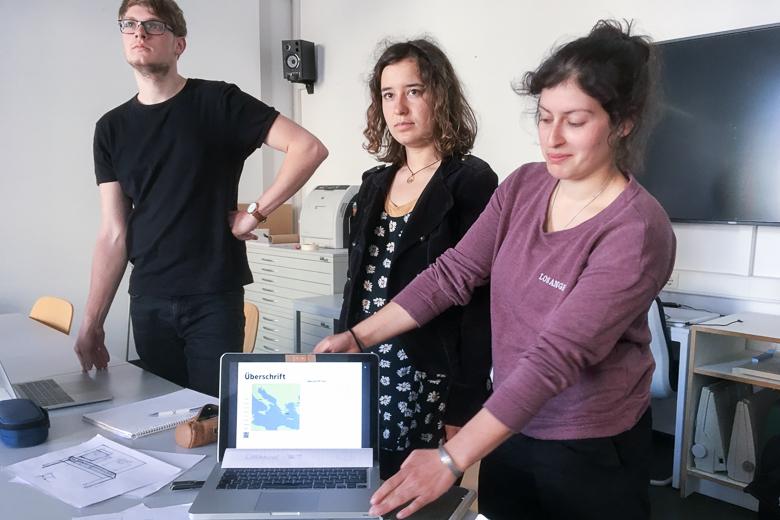 Zu sehen sind drei Personen. Eine Person zeigt einen Entwurf auf einem Laptop in die Kamera.
