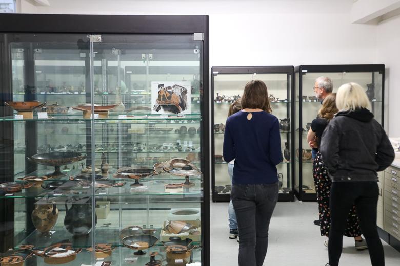 Zu sehen ist ein Raum mit mehreren Glasvitrinen. Darin befinden antike Objekte und Scherben. Mehrere Personen betrachten Objekte in einer Vitrine im Hintergrund.