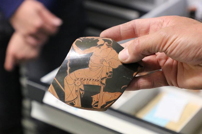Zu sehen ist die Hand einer Person. Sie hält eine antike Scherbe mit einer Darstellung einer Person in der Hand.