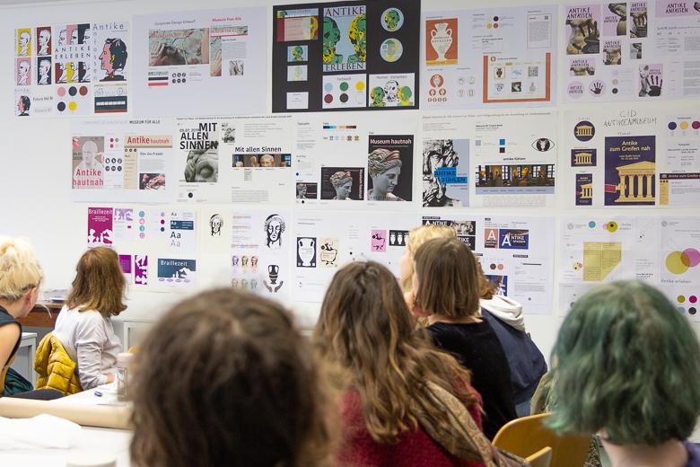 Im Hintergrund sind Entwürfe der Studierenden zu Schrift, Plakat und Farbkonzept der Ausstellung zu sehen. Im Vordergrund sind Studierende zu sehen. Sie haben ihren Blick zu den Entwürfen gerichtet und sind von hinten zu sehen.
