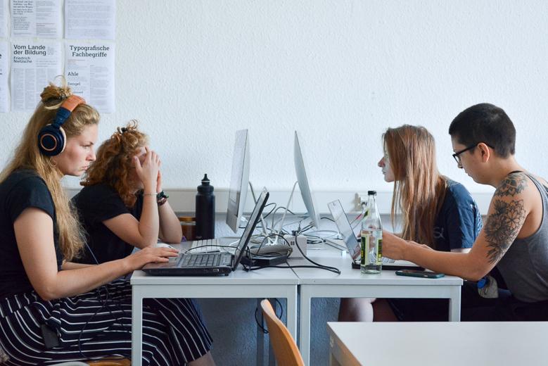 Zu sehen sind vier Studierende. Sie sitzen sich, jeweils vor einem Computer, gegenüber.