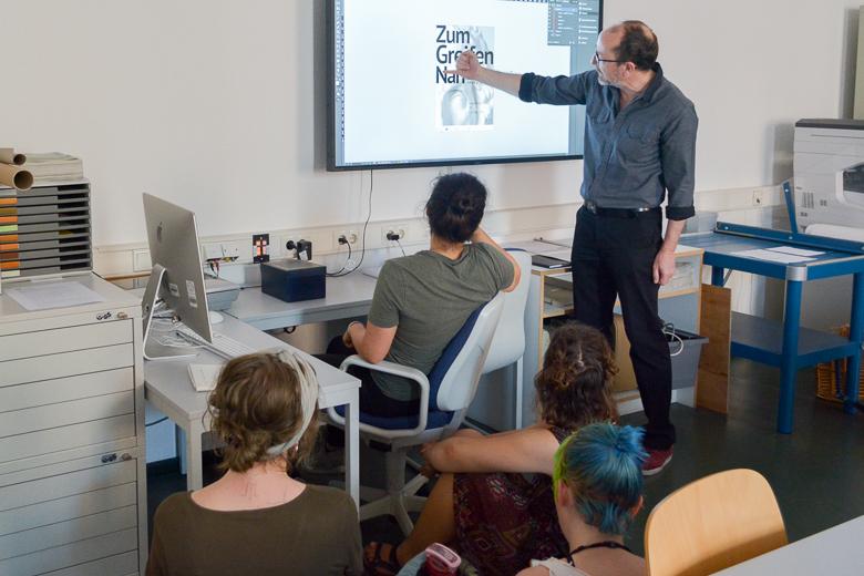 Zu sehen sind vier Studierende von hinten. Eine Lehrperson erläutert an einem Bildschirm die grafischen Elemente des Plakates zur Ausstellung.