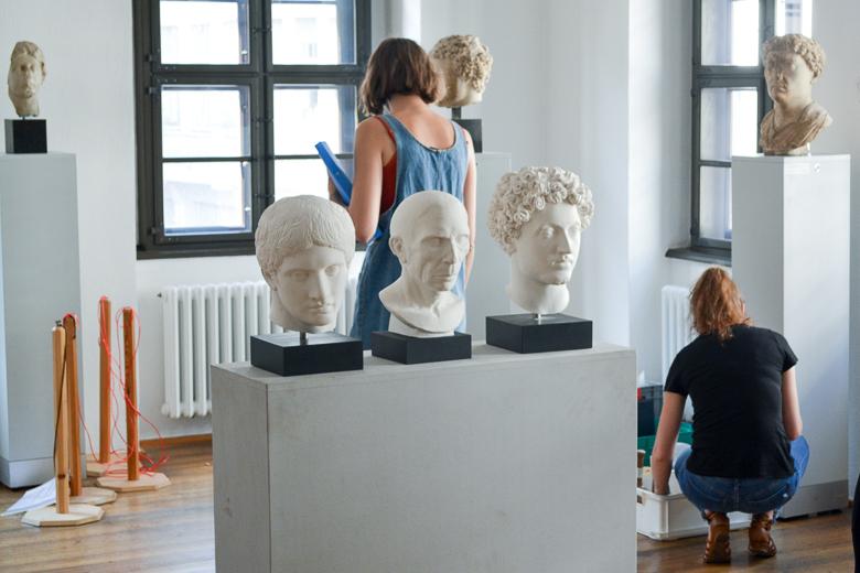 Zu sehen ist eine Ausstellung im Aufbau. Zwei Personen sind damit beschäftigt Ausstellungsobjekte auszupacken. Im Vordergrund stehen drei weiße Büsten auf einem gemeinsamen weißen Sockel.