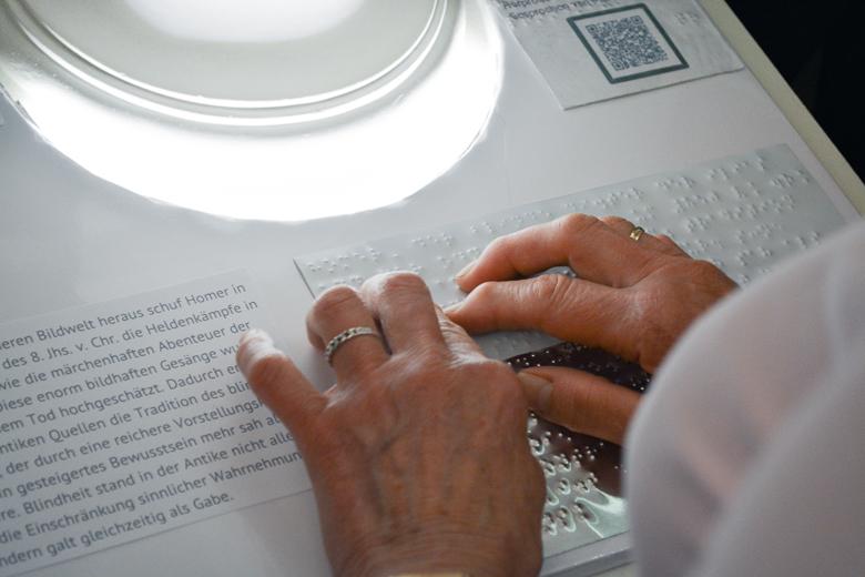 Zwei Hände ertasten einen Text in Brailleschrift auf einem Sockel.