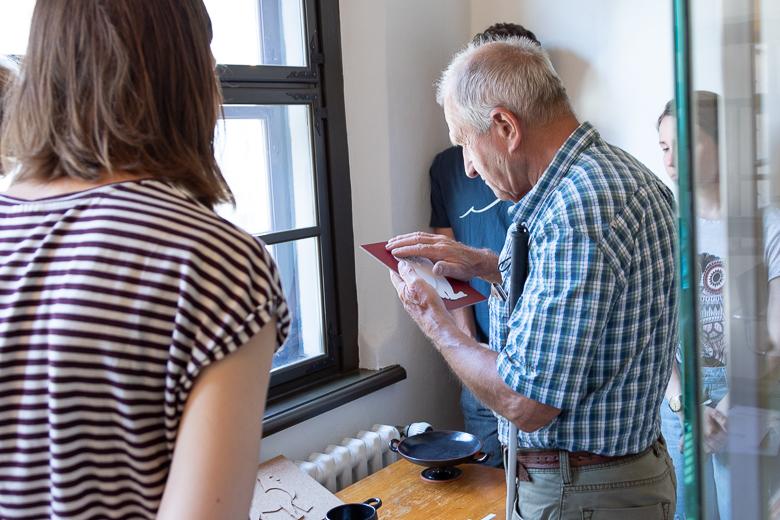 Ein Mann ertastet das Relief einer Eule. Drei Studierende schauen interessiert zu.