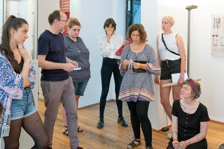 Mehrere Studierende stehen in einem Raum des Museums. Sie diskutieren die Arbeitsergebnisse mit Lehrenden.
