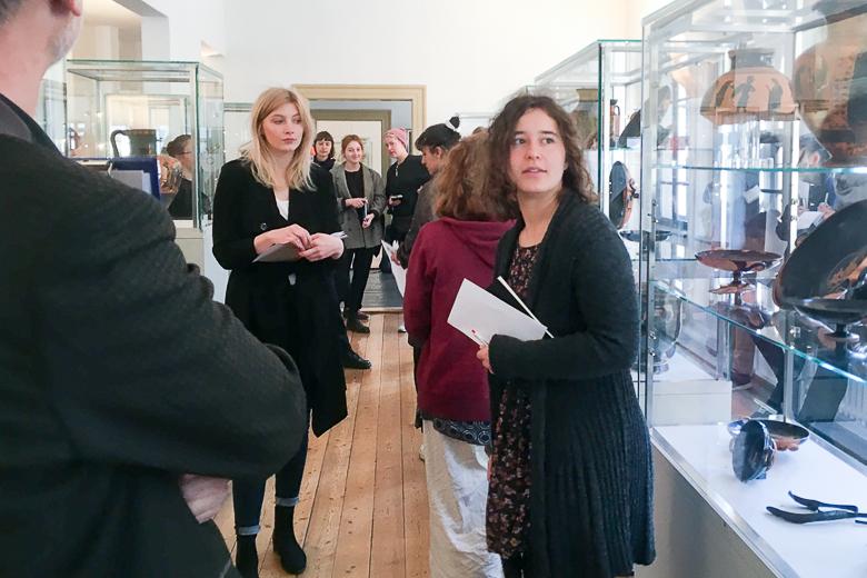 Mehrere Personen sind in einem Gang zwischen mehreren Glasvitrinen mit antiken Ausstellungsobjekten zu sehen.