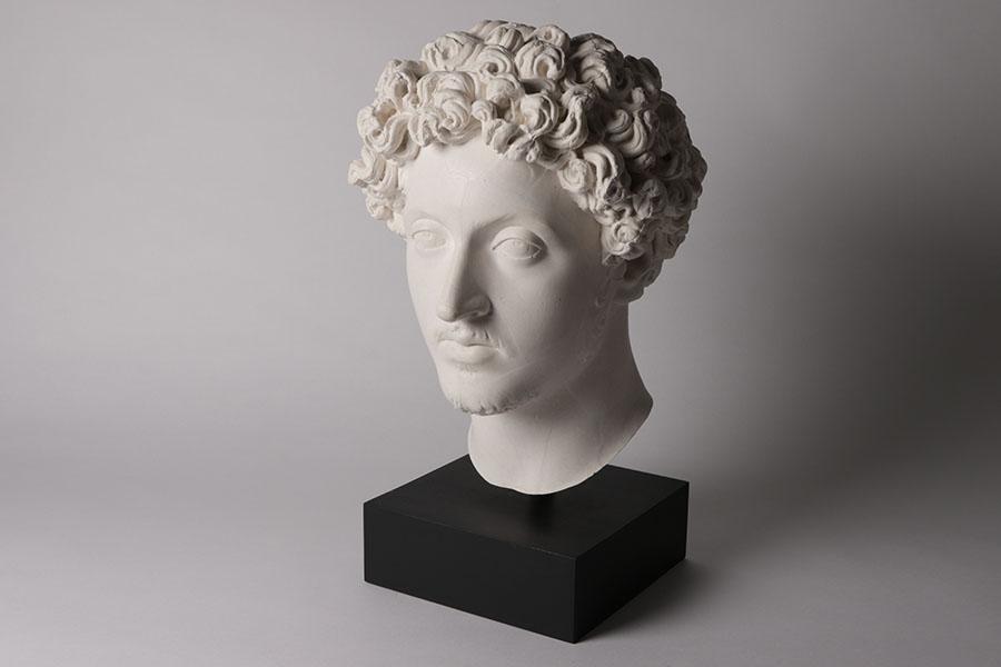 Zu sehen ist ein Kunstmamorabguss des Kopfes von Marc Aurel in weiß auf schwarzem Sockel mit gelocktem Haar und kurzem Bart.