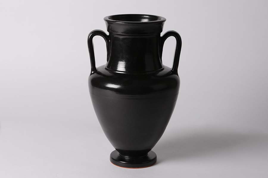Zu sehen ist eine Schwarze symmetrische Vase mit Henkeln rechts und links.
