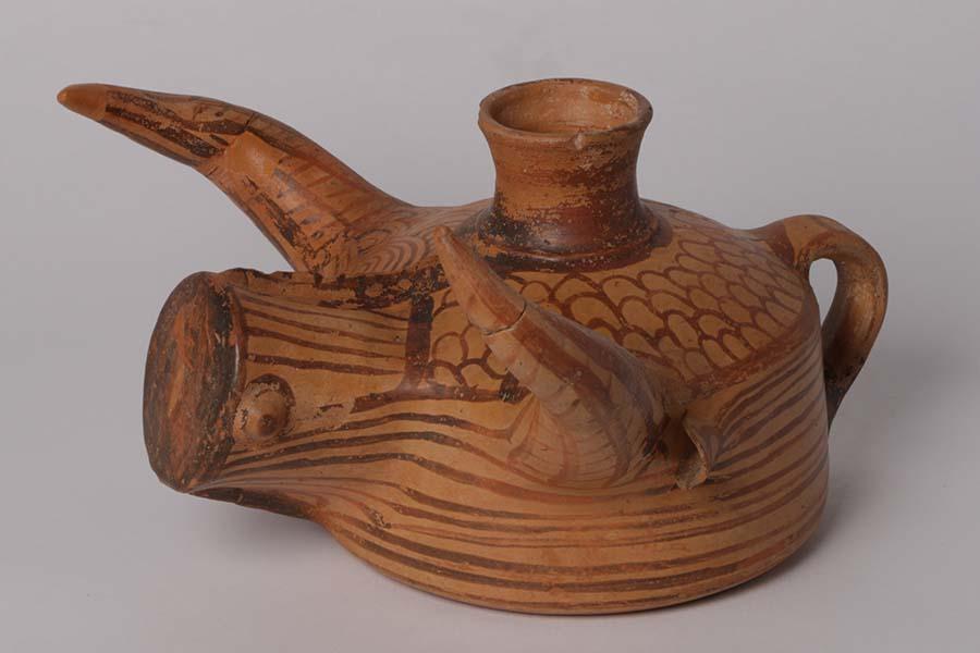 Zu sehen ist eine fein bemalte Statuette eines Stieres aus Ton, in Form einer Vase mit Henkel (links) und Öffnung oben.