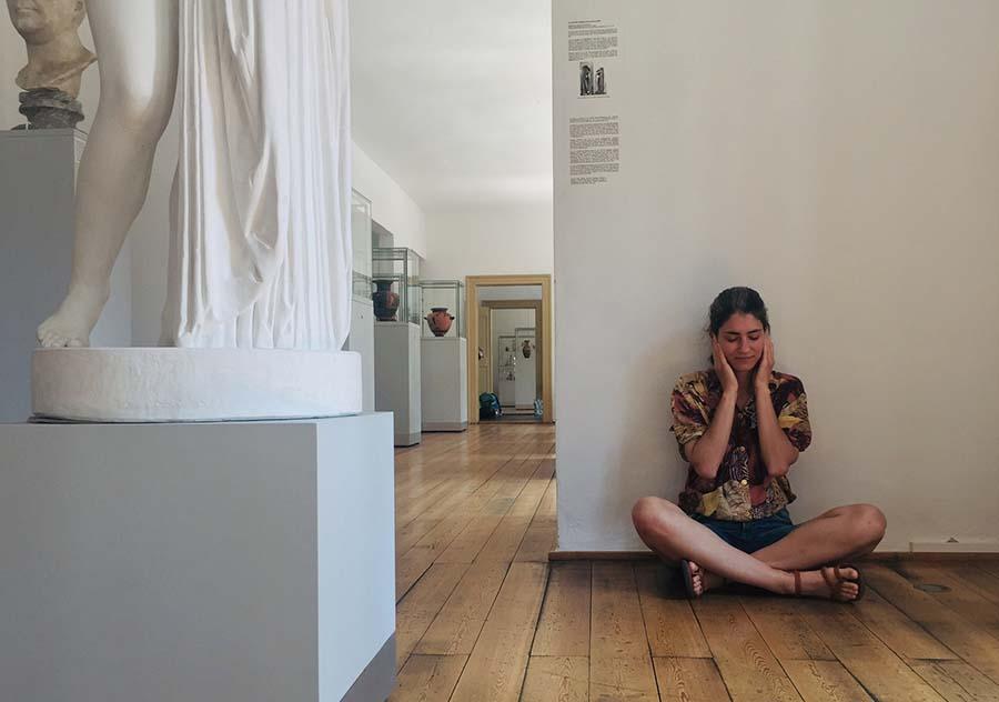 Hier ist im Antikenmuseum,  eine Frau, sitzend im Schneidersitz, zu sehen. Sie lausch mit konzentriertem Blick den Hörstücken.