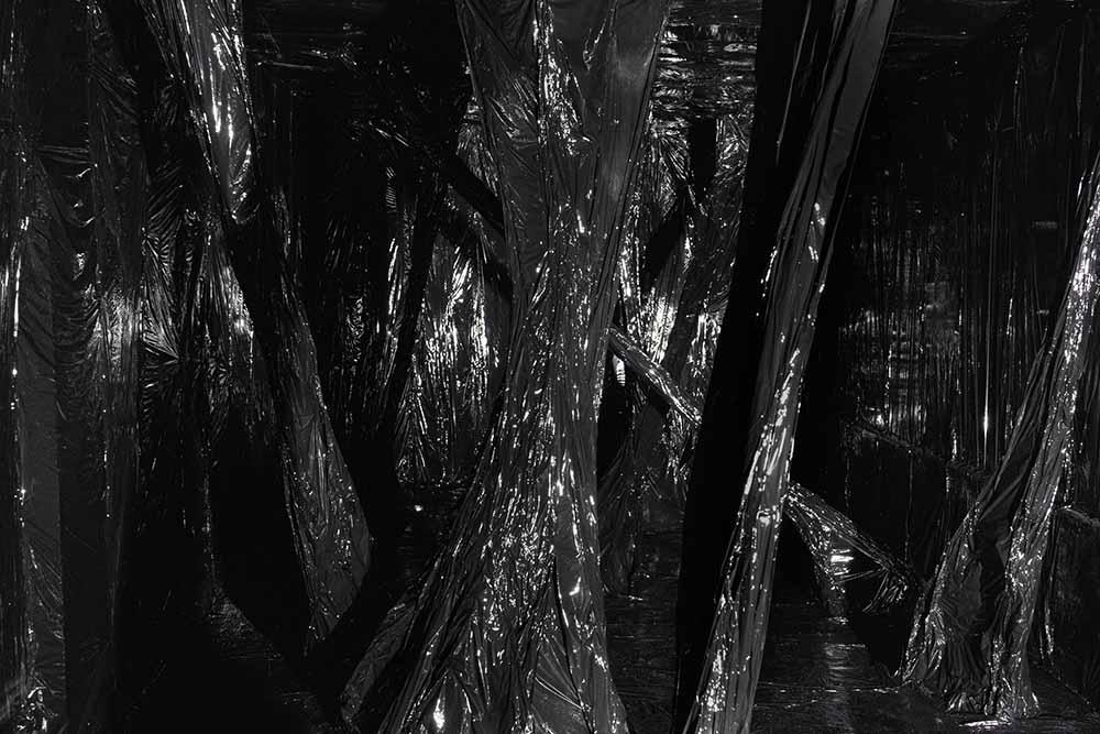 schwarz-weiß Fotografie einer dreidimensionalen Rauminstallation aus stark reflektierender schwarzer Maschinenstrechtfolie