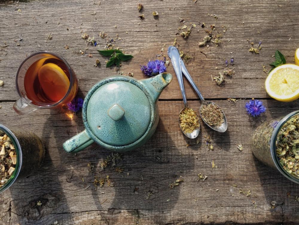 Draufsicht auf einem Holztisch. Dort befindet sich eine Teekanne, eine Tasse und 2 Einmachgläser zu erkenne.