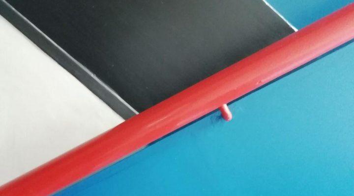 Ein roter Handlauf vor blau schwarz gestreifter Wand